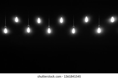 Hanging light bulbs on black background with copy space, black and white photography