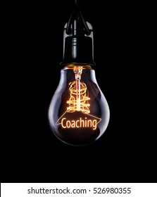 Hanging lightbulb with glowing Coaching concept.