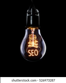 Hanging lightbulb with glowing SEO concept.