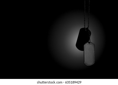 hanging Military ID tags on a dark background