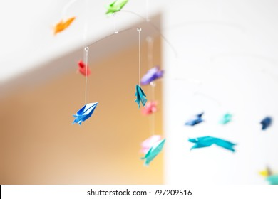 Hanging mobile made from origami rockets. Shaloow depth of field.