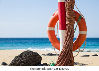 hanging orange life belt with long rope at the beach, security and  safety concept