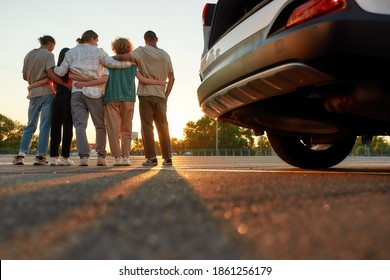 Hanging out. Backs of five young casually dressed friends standing together outside on a parking site casting shadows on a camera with a car on a front line during a beautiful sunrise