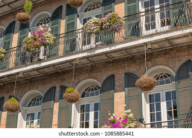Hanging planters and window boxes hanging from a wrought iron balcony in the French Quarter of New Orleans, Louisiana