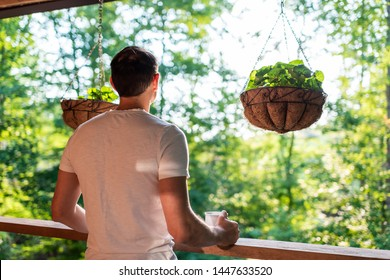 Hanging potted plants with violet flower leaves in spring with man standing on porch of house in morning wooden cabin cottage