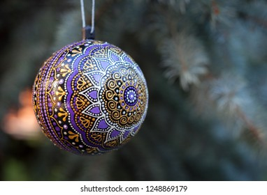 Hanging pupple christmas decoration ball with hand drawn by dots abstract mandala flower and blured pine tree on the background. 2019 New Year celebration wallpaper.