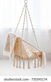 Hanging rattan chair with beige plaid in the house