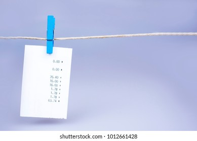 Hanging receipt on a clothesline gray background