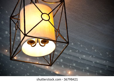 A hanging rectangular lamp with a background of tooling mixed with mini lights from a wedding design.  Plenty of room on the right for copy.  A slight vignette was applied.