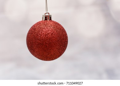 hanging red sparkly Christmas bauble against a blurred cream background.