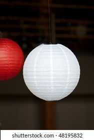 hanging red and white Japanese lantern with dark background