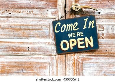 hanging sign Come In We're Open on the wooden door, copyspace on the left.