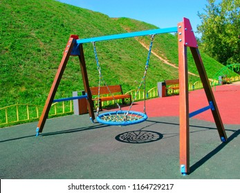Hanging swings at childrens playground. Swings of modern design in the form of a nest with a wicker seat. Children's playground has an artificial soft covering.