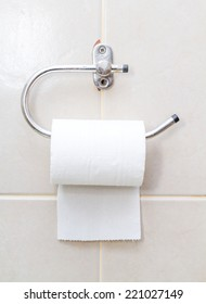 hanging tissue paper on tiles wall in toilet.