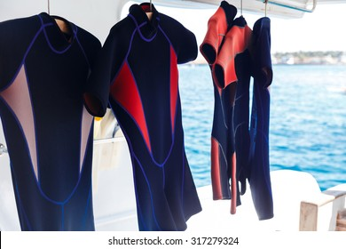 Hanging wetsuits at scuba diving boat waiting for