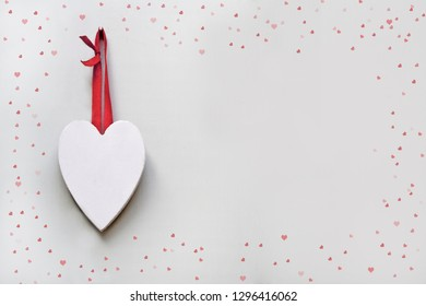 Hanging White Heart with red ribbon surrounded by a border of hearts for Valentines Day