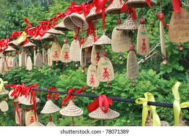 Hanging wish and prayer Chinese ornaments along steel cables over a soft forest background in Yanoda national park. Shallow depth-of-field