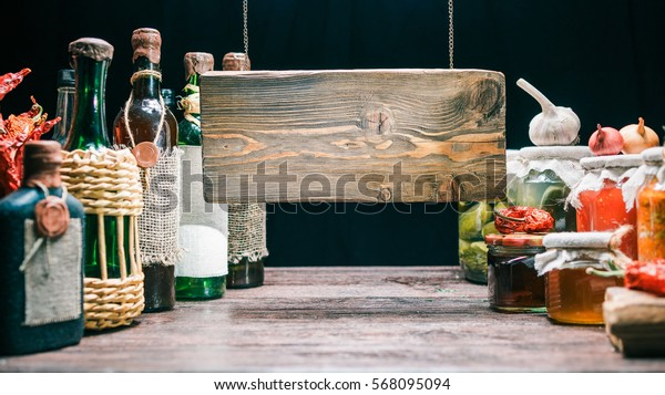 Hanging wood sign of food store. Wine boottles on the left and vegetable cans on the right