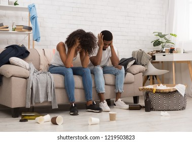 Hangover after house party. African-american couple suffering from headache, holding their heads sitting on couch in messy room