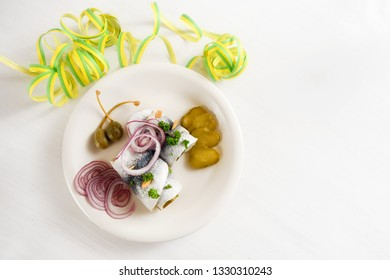 hangover meal, rolled pickled herring, also called rollmops with red onions, gherkins and capers, white table with party streamer, view from above, copy space, selected focus, narrow depth of field