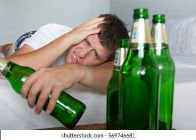 Hangover suffering man close up portrait with bottles of beer. Alcoholism concept.