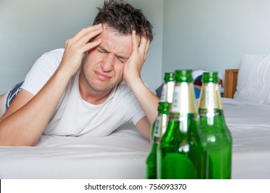 Hangover suffering man holding his aching head close up portrait with bottles of beer. Alcoholism concept.