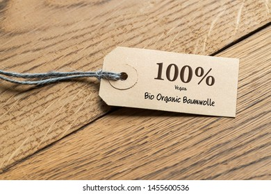 "hangtag with title ""100% Bio Organic  Cotton"" in German on wooden background"