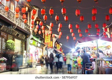 HANGZHOU, CHINA - DECEMBER 2016: Motion blurred chinese tourist street at night with red lanterns.