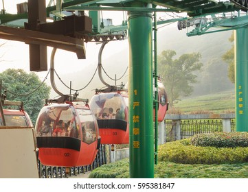 HANGZHOU, CHINA - December 28, 2014: Cable Car with Chinese tourists inside start to rise on the peak.