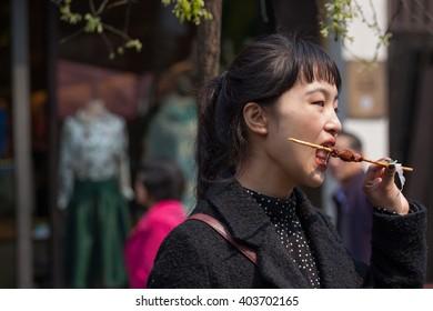 HANGZHOU,ZHEJIANG IN CHINA -MAY 26:Unidentified young girl walking in Hefang street and eat barbeque on MAY,2016 in Hefang street in HANGZHOU,ZHEJIANG IN CHINA.