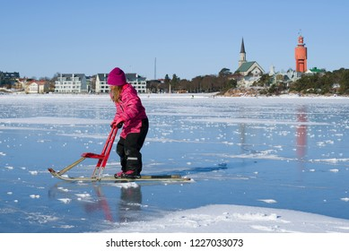 HANKO, FINLAND - FEBRUARY 24, 2018: A girl rides a Finnish sledge on the ice of the Finnish Bay on a sunny winter day