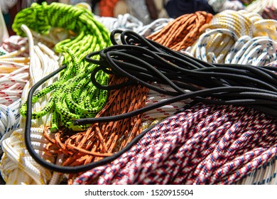 Hanks or coils of modern multi-coloured rope, some arranged neatly, others piled up in an untidy manner. Utilised for many applications, such as mooring lines, halyards or sheets on boats or yachts.