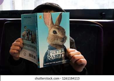 Hanley, Stoke on Trent, Staffordshire - 16th December 2018 - A little boy poses while reading a Peter Rabbit book on a bus from Fenton to Hanley on the First bus service, public transport