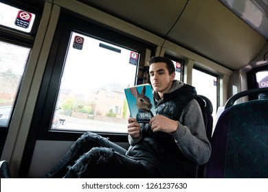Hanley, Stoke on Trent, Staffordshire - 16th December 2018 - A young man reads a Peter Rabbit book on the First bus service to the city centre on a cold wet winter day