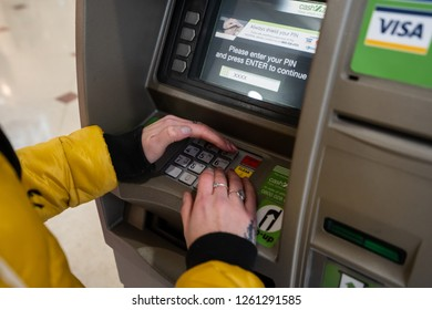 Hanley, Stoke on Trent, Staffordshire - 16th December 2018 - A young women using a cash machine, ATM to withdraw some money at the Intu Potteries Shopping Centre, precinct, mall in the city centre