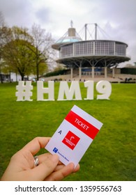 Hannover, Germany - April 2019: Caucasian hand holding a paper entrance ticket to the Hannover Messe inside the fairgrounds