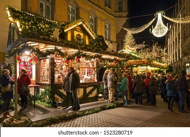 HANNOVER, GERMANY - DECEMBER 8, 2018: Stalls with food and hot drinks on Knochenhauerstrasse at Old Town Christmas Market in dusk. Many unknown people stand at the market stalls and drink mulled wine.