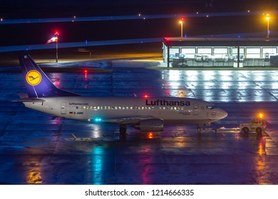 HANNOVER, GERMANY - FEBRUARY 19, 2012: At the apron of Hannover Airport a Boeing737 about to perform a short haul regional Lufthansa flight is being carried away by a pushback tractor on a rainy night