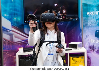 Hannover, Germany - March, 2017: Girl playing video game in virtual reality headset and handheld controllers developed by HTC Vive on exhibition Cebit 2017 in Hannover Messe, Germany