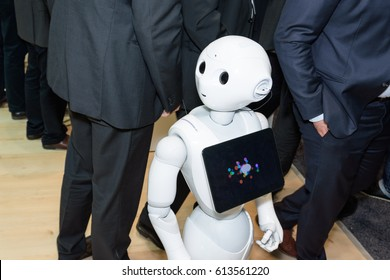 Hannover, Germany - March 22, 2017: The humanoid robot Pepper from SoftBank Group between men in suits at ibm booth on CeBIT 2017. CeBIT is the world's largest trade fair for information technology.