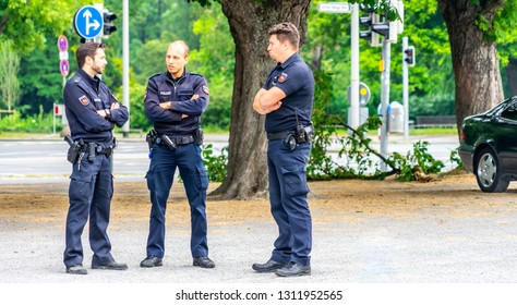 Hannover, Germany, May 19., 2018: Three German policemen in dark blue uniforms are standing with crossed arms on the sidewalk next to a street.