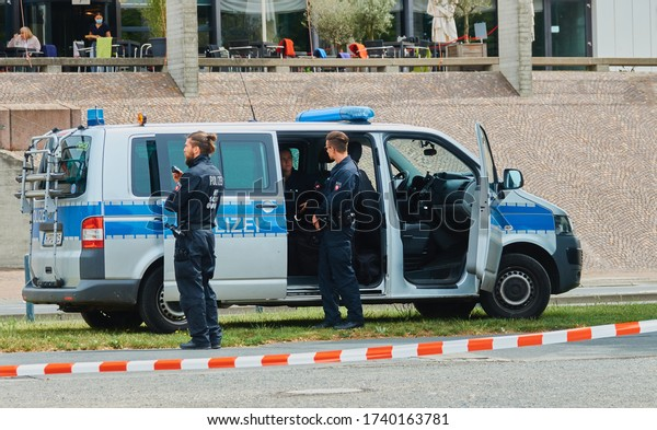 Hannover, Germany, May 23., 2020: Police car with policemen waiting in front of it at the edge of a demonstration behind a barrier