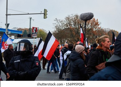 Hannover, Germany, November 23., 2019: Demonstration of the right-wing extremist National Socialist NPD with old black-white-red flags of the German Reich behind police officers and reporters