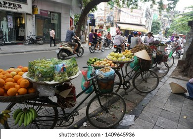 Hanoi City / Vietnam - 12 Sep 2015: Unknown sellers in Old Streets at Hanoi City. They sell fruits such as orange, bananas, vegetables... & displayed them on open and low baskets or hang long bicycles