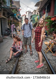 Hanoi City / Vietnam - May, 26, 2019: A Family of Confused Ukrainian Tourists and Other Tourists are Waiting for the Train on the Narrow Railway Street in Hanoi Old Quarter