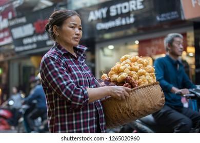 Hanoi, Hoan Kiem, Vietnam - 11/28/2018: Street vendor of Hanoi looking for buyers of her homemade produce.