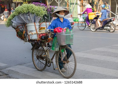 Hanoi, Hoan Kiem, Vietnam - 11/28/2018:  Vendor with fresh flowers. Street vending has existed in Hanoi for hundreds of years. Many  use bicycles to go around.