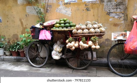 Hanoi Old Quater. Street Vendor. Fresh Fruits on a bike, leaning on a yellow wall