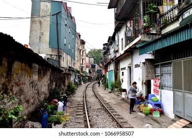 Hanoi, Vietnam - 03 21 2018: Train railway leading through narrow street in Hanoi