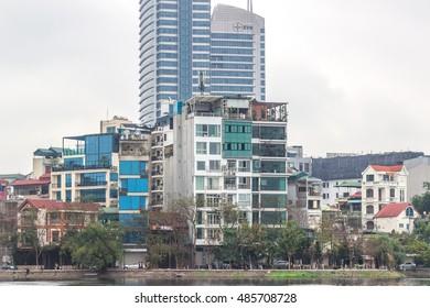 HANOI, VIETNAM - 11 MARCH 2016. Tall skyscraper tower in the back of poor slum houses in Hanoi near the lake